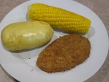 Gepofte aardappel, verse maiskolf en gepaneerde filet
